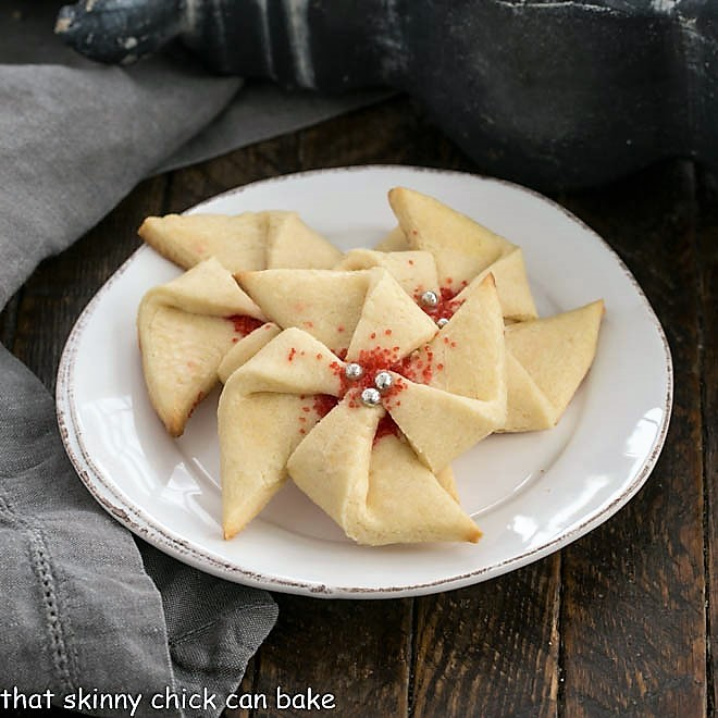 3 Poinsettia Cookies on a small white dessert plate