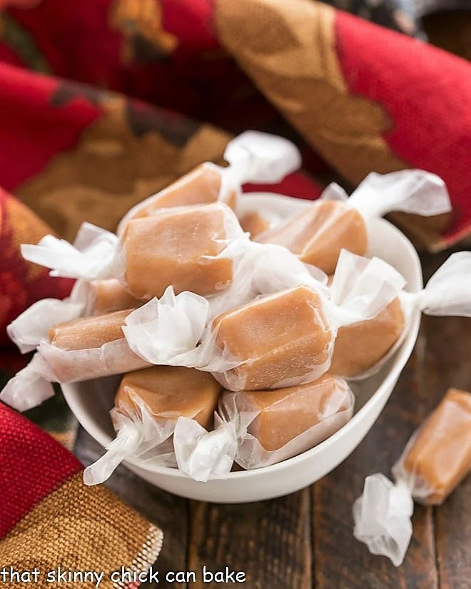 Homemade Caramels wrapped in waxed paper in a white candy bowl