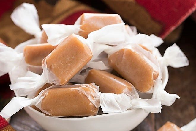 Homemade brown sugar caramels wrapped in wax paper in a white bowl