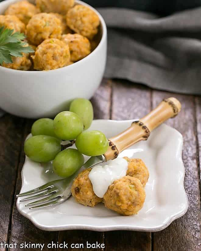 Buffalo Chicken Meatballs on a small white plate topped with blue cheese sauce