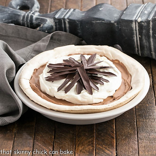 Chocolate Angel Pie topped with whipped cream and chocolate shards in a white pie plate