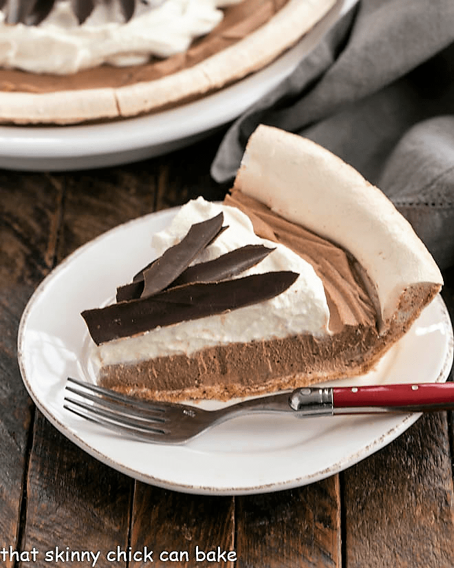 Slice of chocolate angel pie on a round white plate with a red handled fork