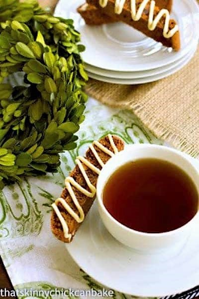 Gingerbread Biscotti on a stack of saucers and with a cup of tea