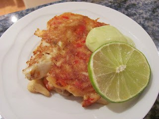 one crab cake on a white plate garnished with a lime slice and ailoli