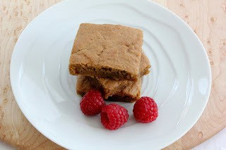 Chewy, tasty Butterscotch brownies on a white plate with raspberries