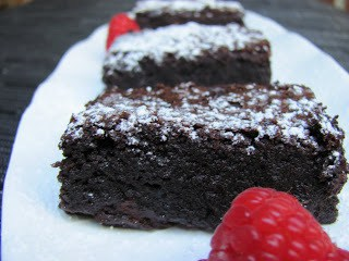 Brownies on a white tray with fresh raspberries