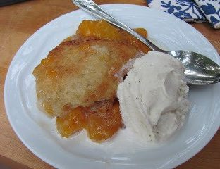 Peach cobbler and ice cream on a white plate with a spoon