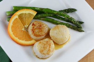 Overhead view of Scallops with Caramel Orange Sauce on a white plate with asparagus and orange slices