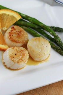 3 Scallops withCaramel Orange Sauce on a white dinner plate