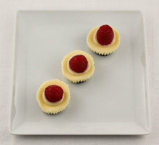 MIni White Chocolate Cheesecakes topped with raspberries on a white tray