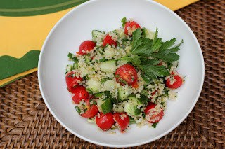 Overhead view of tabbouleh recipe in a white bowl garnished with parsley