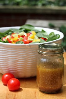 Gazpacho spinach salad in a white serving bowl with a mason jar of salad dressing