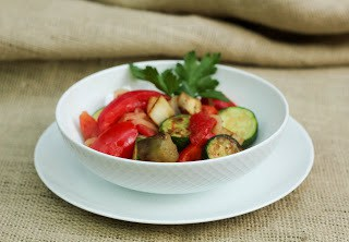 Side view of ratatouille with a sprig of parsley on in a white bowl