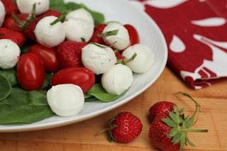White oval platter of mozzarella, tomato and strawberry salad