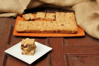 Stack of chocolate chunk bars on a square white plate in front of a cutting board full of sliced bar cookies