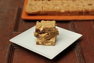 Stack of chocolate chunk bars on a white square plate in front of a cutting board