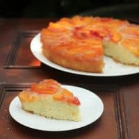 Peach upside down cake with a slice on a plate in the foreground