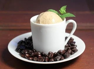 Two scoops of coffee ice cream in a coffee mug with a sprig of mint