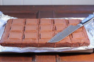 Slab  of brownies on a cutting board with a knife