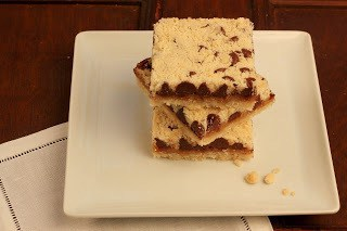 Stack of chocolate caramel streusel bars on a white plate