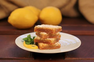 Stack of 4 graham crusted lemon bars on a dessert plate with lemons in the background