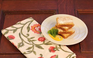 Distance view of a stack of lemon bars on a floral napkin