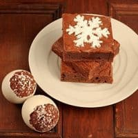 Stack of brownies on a white place next to egg shaped brownies in shells