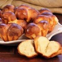 Brioche roll split open in front of a tray of rolls