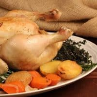 Armagnac Chicken on a white platter with vegetables and herbs