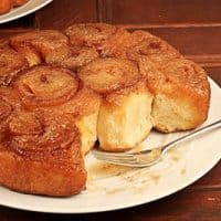 A plate partially eaten maple syrup sticky buns