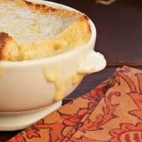 A close up of cheese topped onion soup
