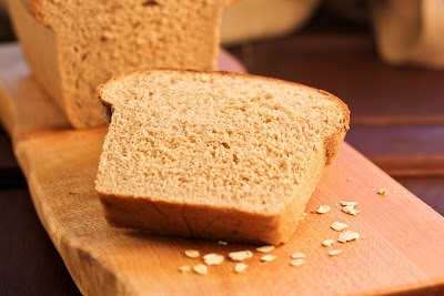 Slice of honey oatmeal bread surrounded by a few oats on a wooden cutting board