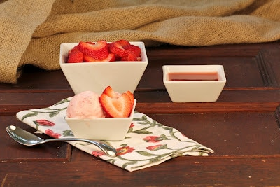 Small white bowl filled with strawberry mascarpone ice cream and fresh strawberry slices