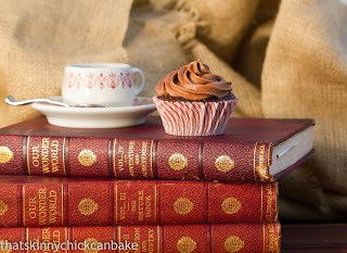 A Classic Chocolate Cupcakes with Chocolate Buttercream on a stack of books with a cup of tea