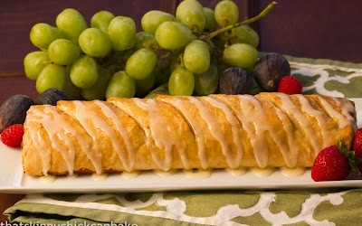Apple strudel on a white tray with grapes in the background