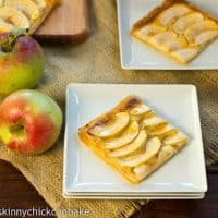 Two Apple Almond Tarts on white serving plates.