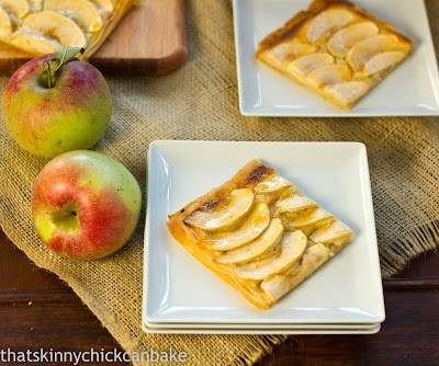 Apple Almond Tart on two white square serving plates with apples on the side.