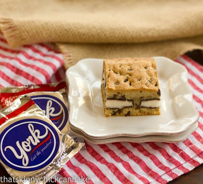 A peppermint stuffed chocolate chip cookie bar on a stack of plates with a couple york peppermint patties