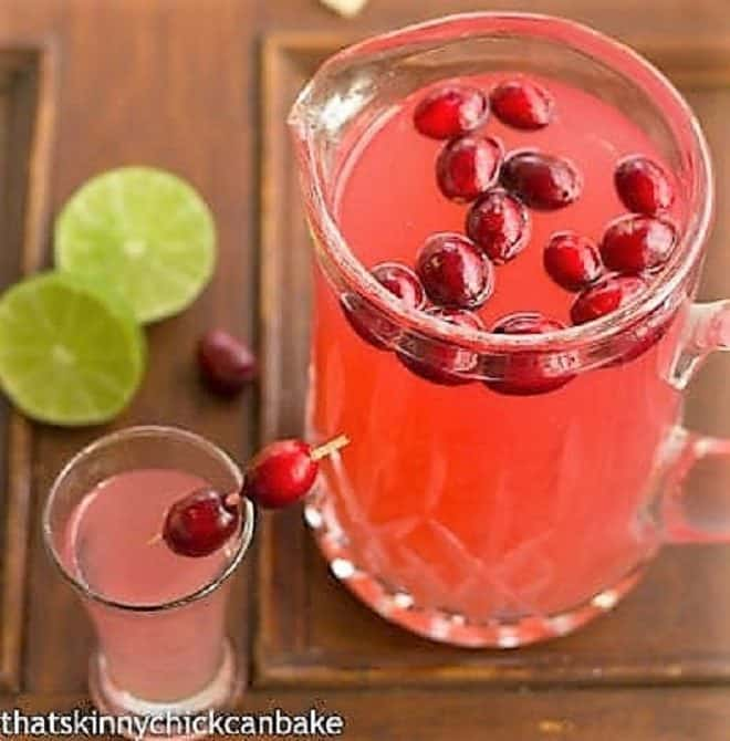 Pear cosmos in a glass pitcher with fresh cranberry garnish