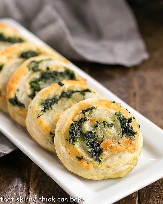 Muenster and Spinach Pinwheels lined up on a white, rectangle ceramic tray