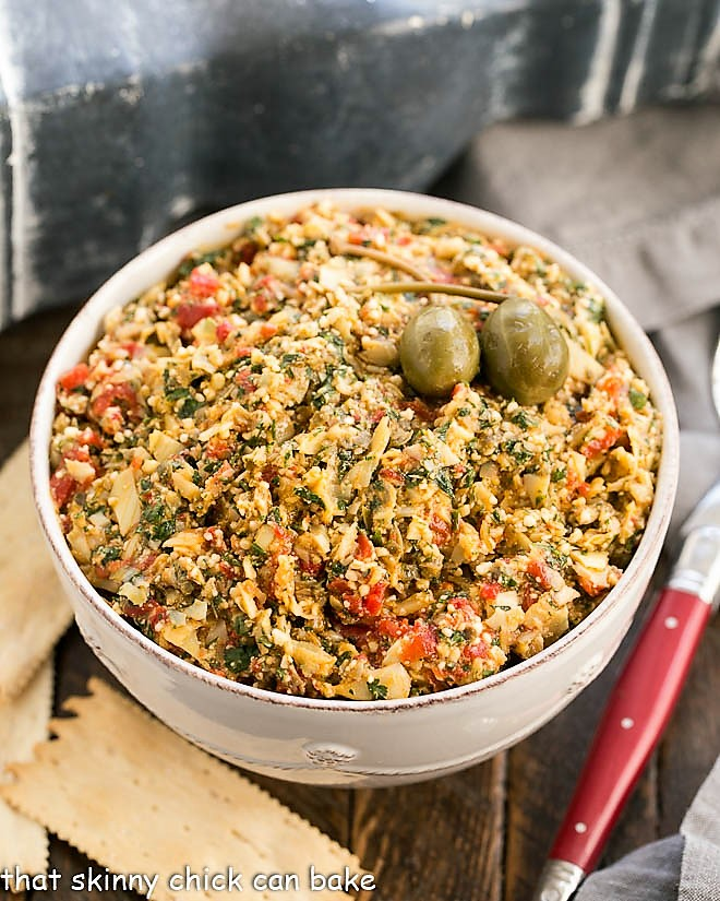 Overhead view of this artichoke tapenade with a red handled spoon