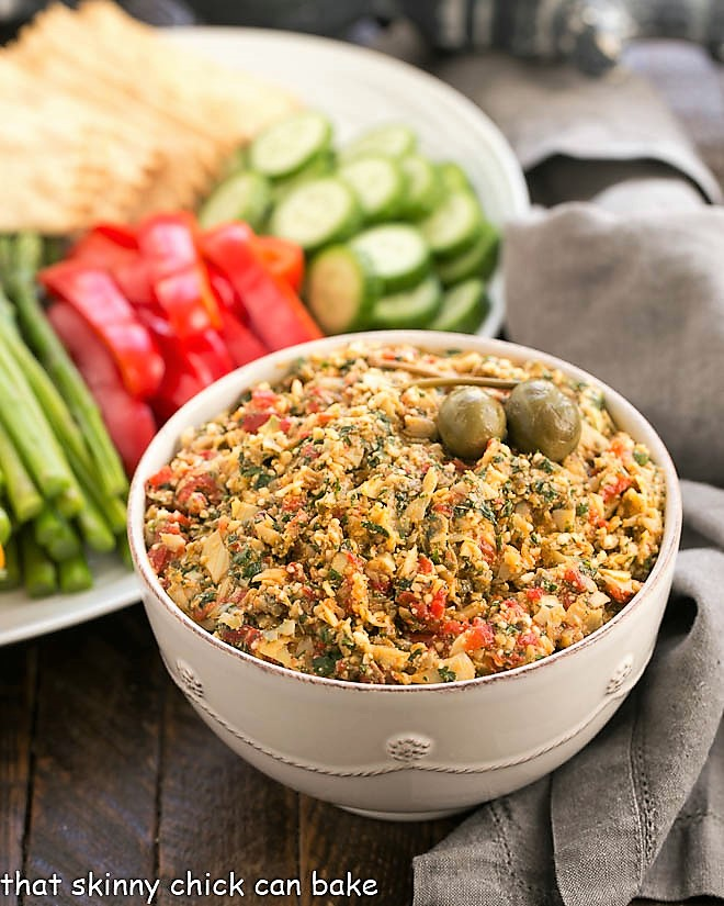 Bowl of Red Pepper Artichoke Tapenade with a platter of fresh vegetables