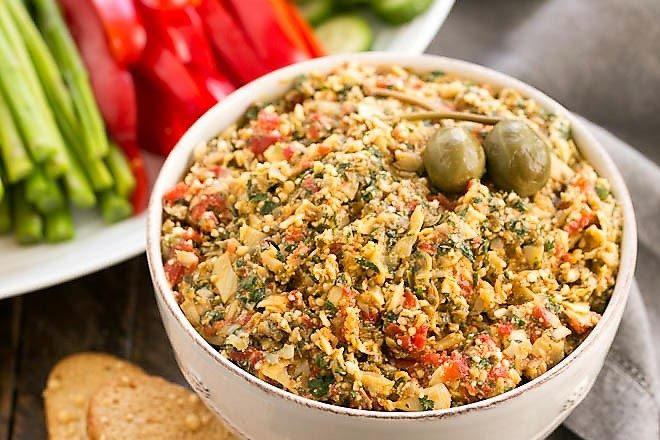 Roasted Red Pepper Artichoke Tapenade in a white bowl with a tray of crudite