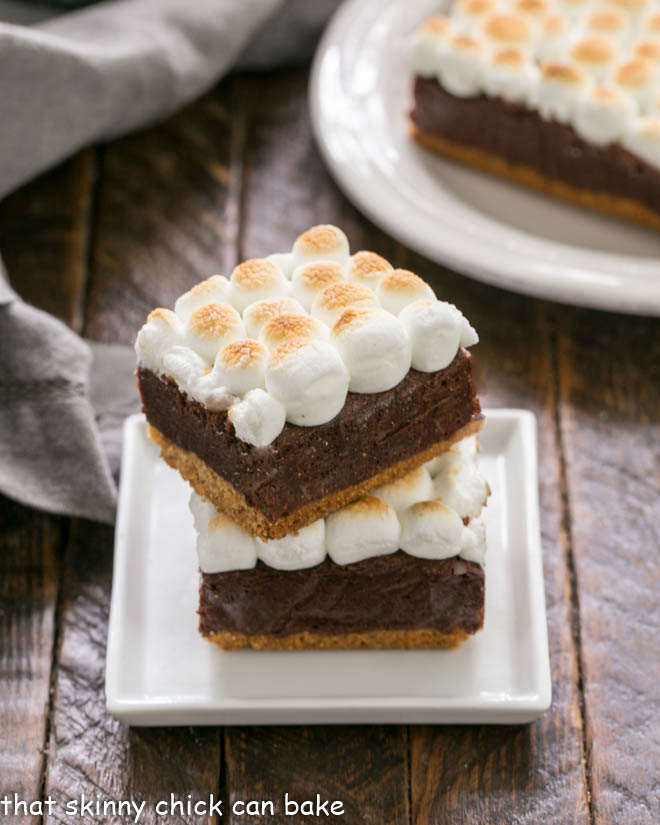 S'mores Brownies with a graham cracker crust stacked on a small square white plate