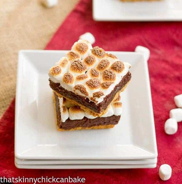 S'mores Brownies with a graham cracker crust stacked on small white plates