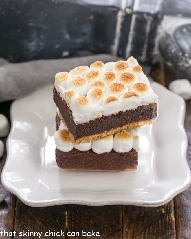 two s'mores bars stacked on a square white plate