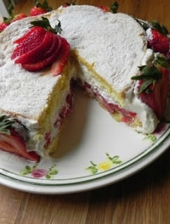 Summer strawberry cake with a slice removed