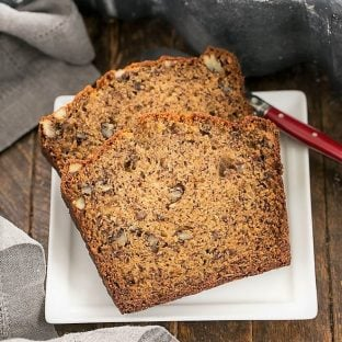 Two slices of the best banana bread on a square white plate
