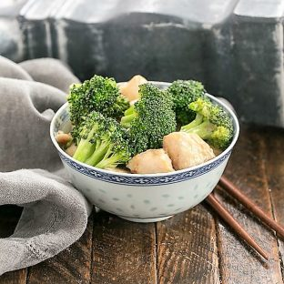 Chicken and Broccoli Stir Fry in a blue and white bowl with wooden chopsticks