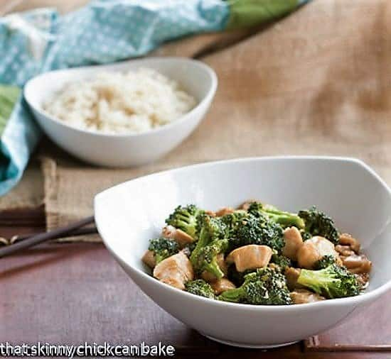 Chicken and Broccoli Stir Fry in a white bowl with a bowl of rice in the background